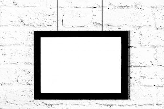 Cadre photo noir horizontal accroché au mur de briques. maquette avec espace de copie Photo Premium