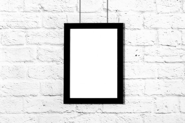 Cadre photo noir vertical accroché sur un mur de briques. maquette avec espace de copie. Photo Premium