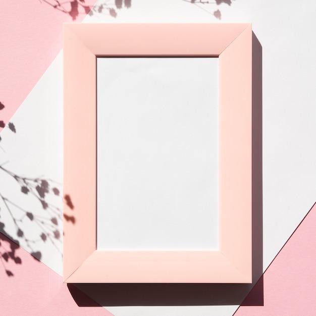 Cadre photo rose sur un blanc vierge avec une ombre de branche sur un fond rose Photo gratuit