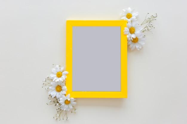Cadre photo vide avec vase à fleur devant un fond blanc Photo gratuit