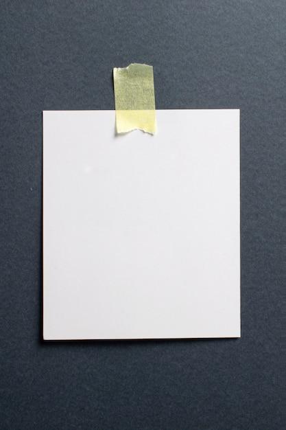 Cadre Photo Vierge Avec Des Ombres Douces Et Du Scotch Jaune Sur Fond De Papier Kraft Noir Photo gratuit