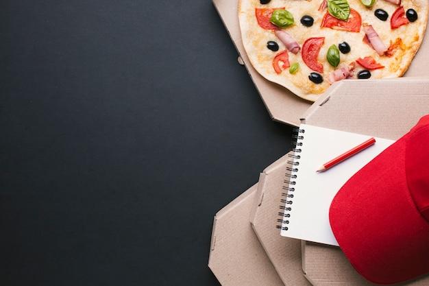 Cadre de pizza vue de dessus avec capuchon rouge et cahier Photo gratuit