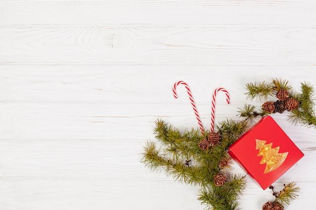 Cadre plat avec cadeau et branches Photo gratuit