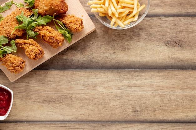 Cadre plat avec nourriture pour poulet et frites Photo gratuit