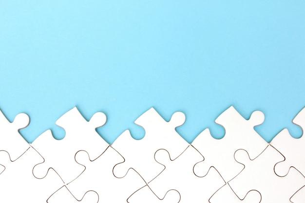 Cadre de puzzle blanc sur fond bleu pastel avec espace de copie Photo Premium