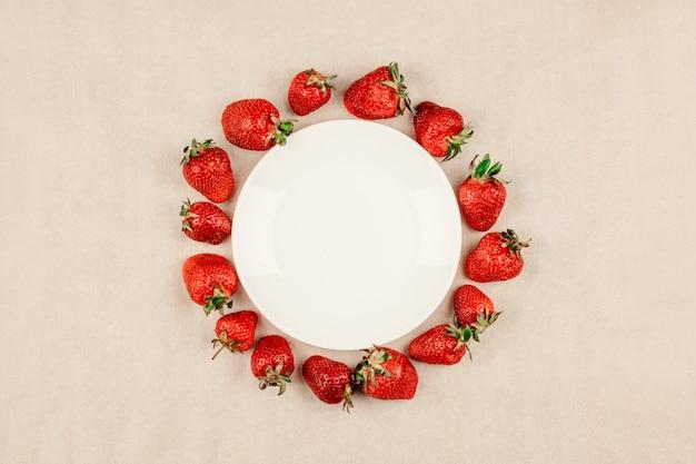Cadre rond aux fraises et assiette blanche vide Photo Premium