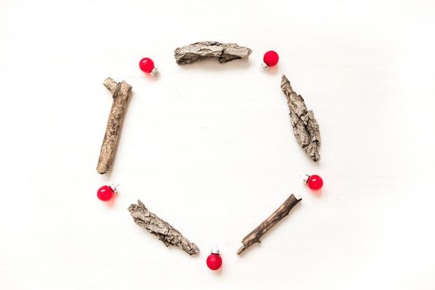 Cadre rond en écorce, cônes de sapin et boules rouges. composition de laïque plat de noël d'hiver Photo Premium
