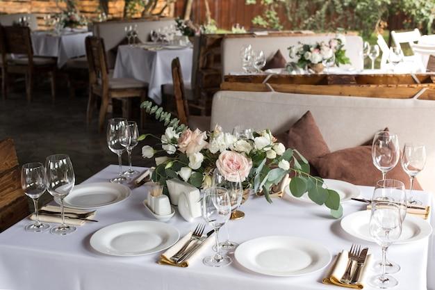 Cadre de table de mariage décoré de fleurs fraîches. table de banquet pour les invités à l'extérieur avec vue sur la nature Photo Premium