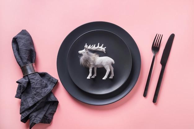 Cadre de table de noël noir avec des rennes sur fond rose. vue de dessus. Photo Premium
