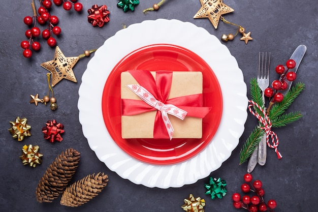Cadre De Table De Noël Avec Plaque Rouge, Boîte-cadeau, Couverts Avec Un Arc De Décorations Festives Sur Fond De Pierre Photo Premium