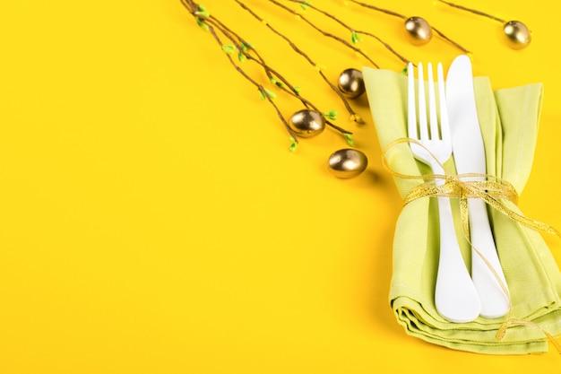 Cadre de table de pâques avec des couverts de cuisine sur un fond jaune vif Photo Premium