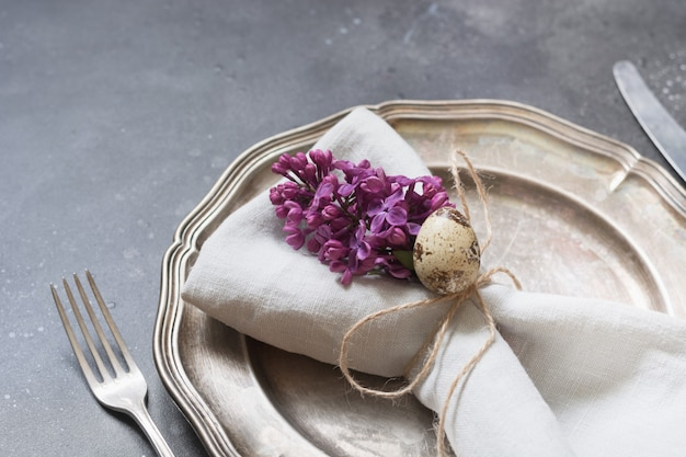 Cadre de table de pâques avec des fleurs lilas sur noir. Photo Premium