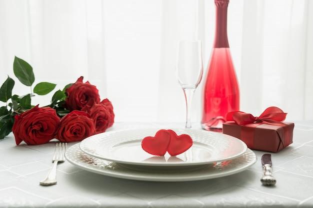 Cadre de table saint valentin avec roses rouges et champagne. invitation pour une date. Photo Premium