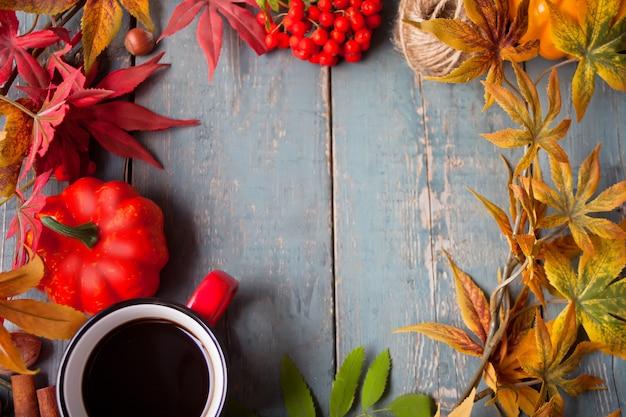 Cadre avec une tasse de café avec des feuilles d'automne et petites citrouilles Photo Premium