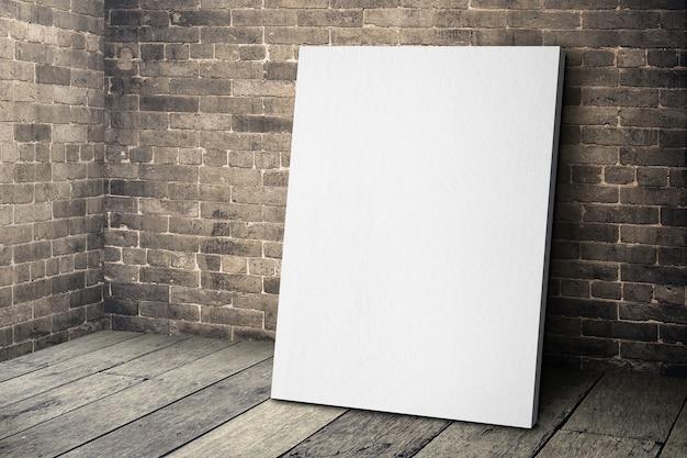 Cadre De Toile Blanc Vierge Se Penchant Sur Le Mur De Briques Grunge Et Plancher De Bois Photo Premium