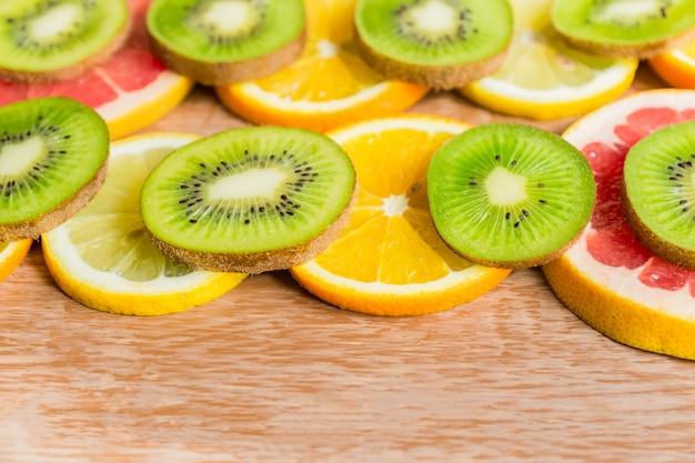 Cadre Avec Tranche D'oranges, Citrons, Kiwis, Pamplemousses Sur Table En Bois Photo Premium