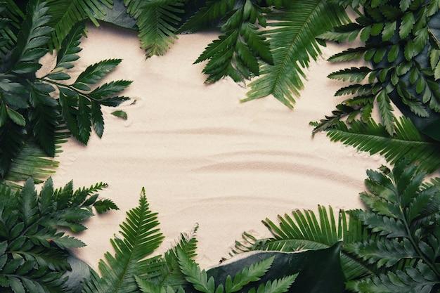 Cadre Tropical En Feuilles De Palmier Avec Espace Copie Sur Fond De Sable. Mise à Plat Photo Premium