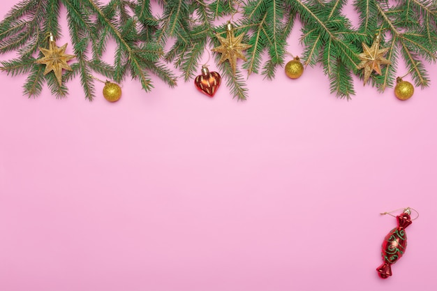 Cadre de vacances de décorations de noël sur fond rose avec une branche de sapin Photo Premium