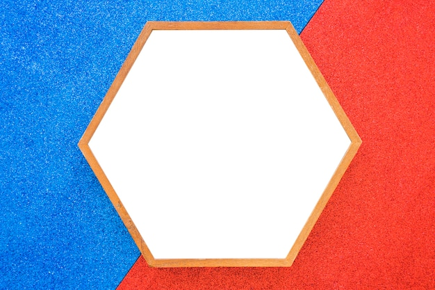 Un cadre vide en bois à six pans creux sur fond rouge et bleu Photo gratuit