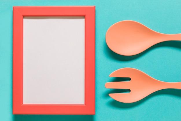 Cadre Vide Avec Une Cuillère Et Une Fourchette Sur Fond Bleu Photo gratuit