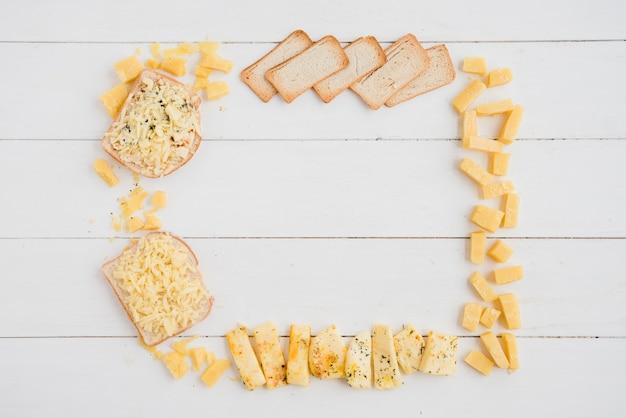 Un cadre vide fait avec du fromage et du pain sur le bureau blanc Photo gratuit