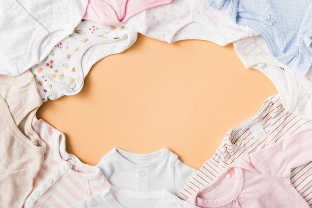 Un cadre vide fait avec des vêtements de bébé sur un fond orange Photo gratuit