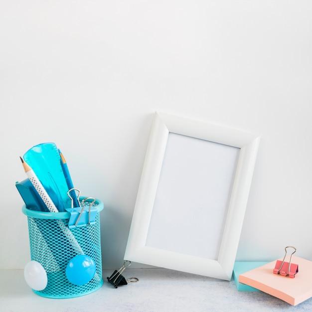 Cadre vide et papeterie sur le bureau Photo gratuit