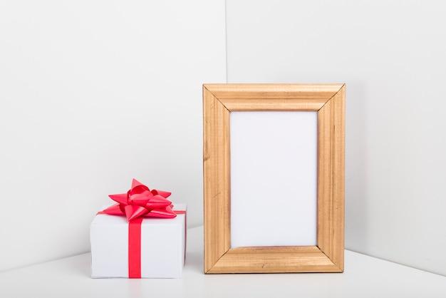 Cadre vide avec petite boîte-cadeau sur la table Photo gratuit