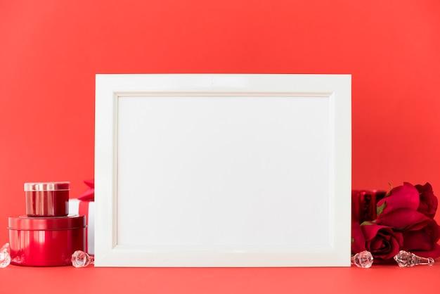 Cadre vide avec des roses rouges sur la table Photo gratuit
