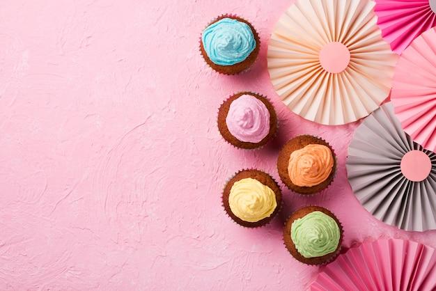 Cadre Vue De Dessus Avec Des Muffins Glacés Sur Fond Rose Photo gratuit