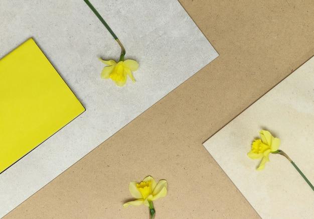 Cadres géométriques avec des fleurs jaunes, des notes sur la table en pierre et en bois Photo Premium