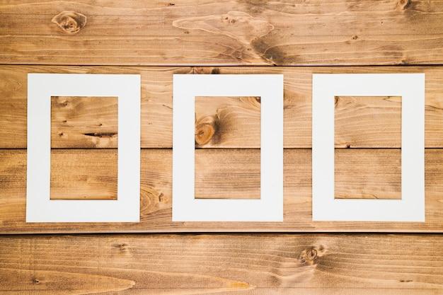 Cadres vides blancs avec fond en bois Photo gratuit