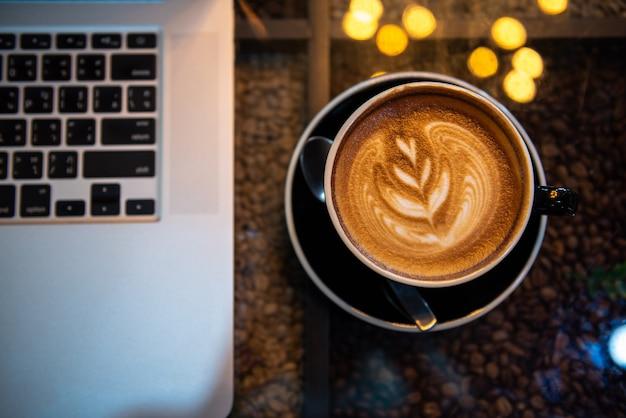 Café d'art de latte dans la tasse noire avec l'ordinateur portable sur la table, ton foncé Photo Premium