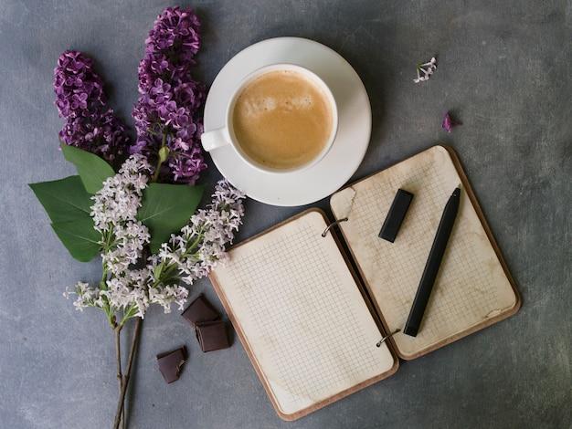 Café, cahier et fleur lilas sur table grise. bureau de travail femme. Photo Premium