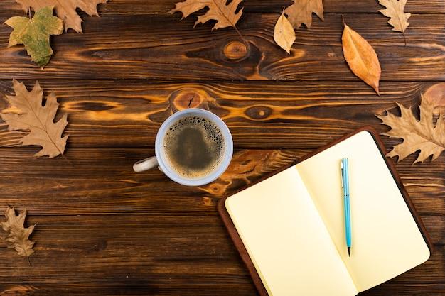 Café et cahier sur fond en bois Photo gratuit