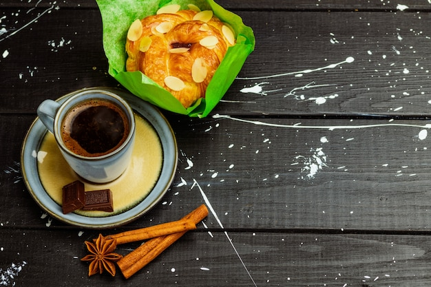 Café à la cannelle et un gâteau sur une table en bois noire Photo Premium