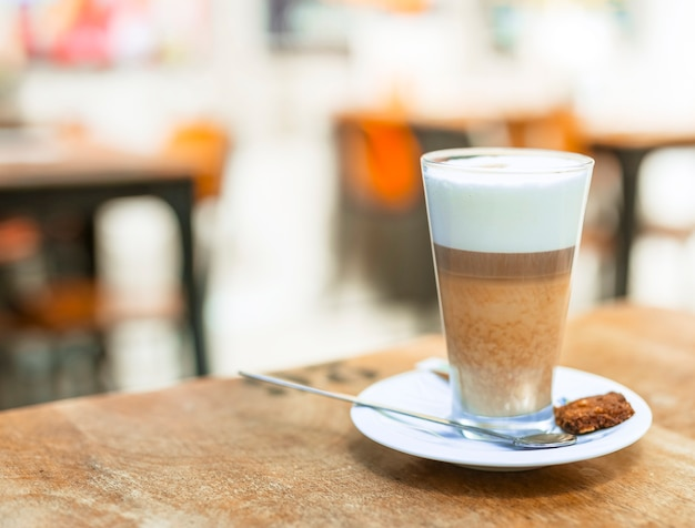 Café cappuccino dans un verre transparent sur table Photo gratuit