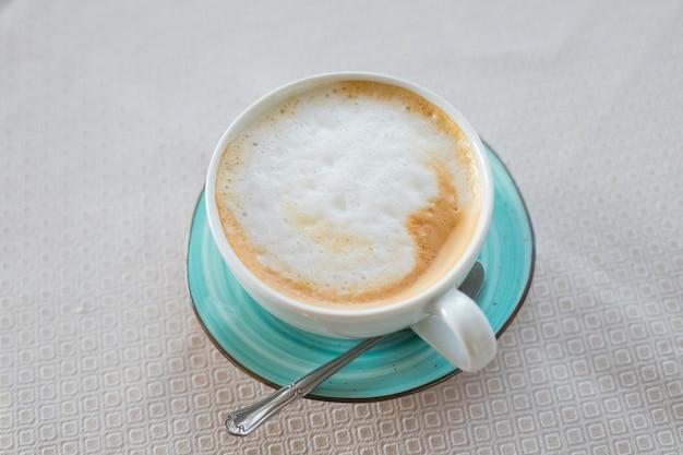 Café Chaud Cappuccino Latte Art En Tasse De Couleur Jade Isolé Sur Table Beige.cappuccino Tasse à Café Vue De Dessus.latte Art Sur Mousse Laiteuse.boisson énergisante Italienne Chaude Servie Dans Une Tasse En Céramique Verte Photo Premium