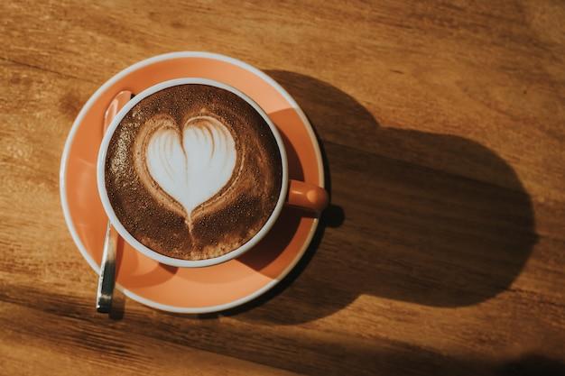 Café chaud dans une tasse sur la table en bois flou, effet rétro tonique. Photo Premium