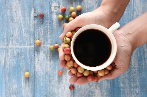 Café dans une tasse blanche avec des grains de café frais à la main. Photo Premium