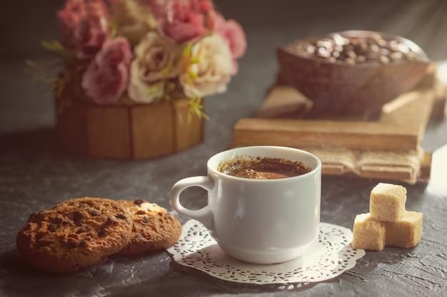 Café du matin avec des biscuits et des morceaux de sucre de canne dans le rayon de soleil. Photo Premium