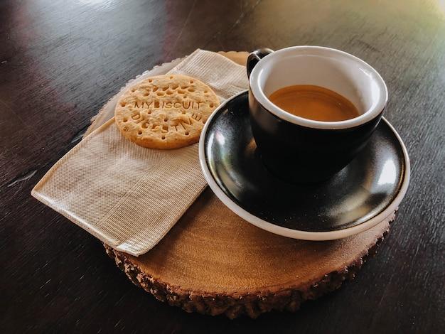 Café du matin dans une tasse noire et des biscuits sur une planche à découper en bois Photo Premium