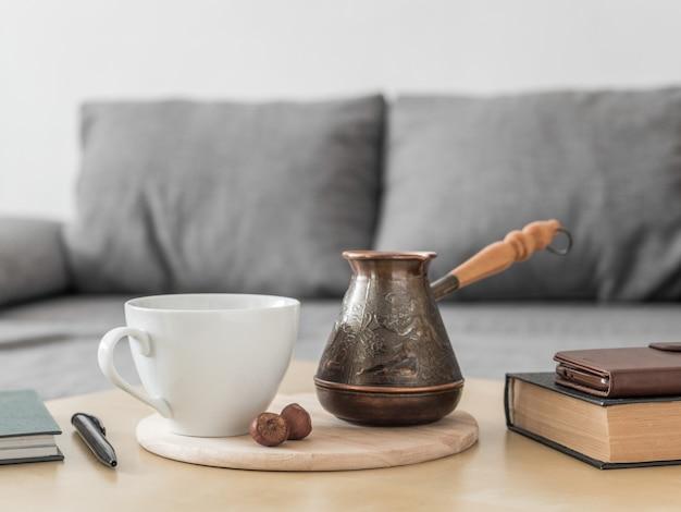 Café Du Matin Encore La Vie à L'intérieur. Tasse à Café, Cezve Et Livres Sur Table, Fond De Canapé Gris. Restez à La Maison Concept De Boisson De Petit Déjeuner. Photo Premium