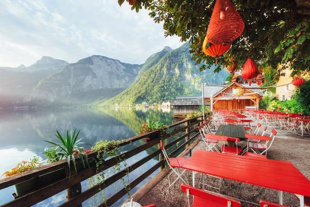 Café d'été sur le magnifique lac entre les montagnes. alpes. hallstatt. l'autriche Photo Premium