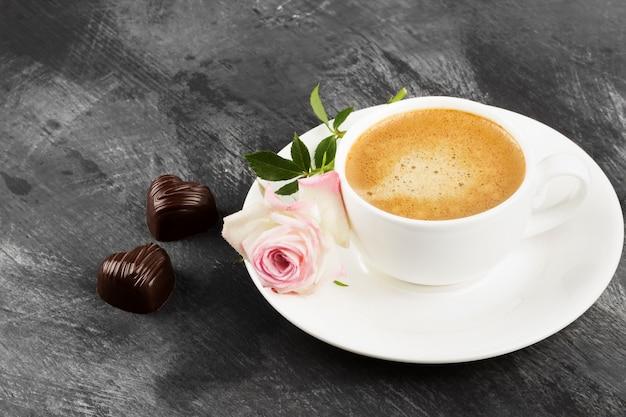 Café Expresso Dans Une Tasse Blanche, Une Rose Rose Et Des Chocolats Sur Fond Sombre. Espace Copie Photo Premium