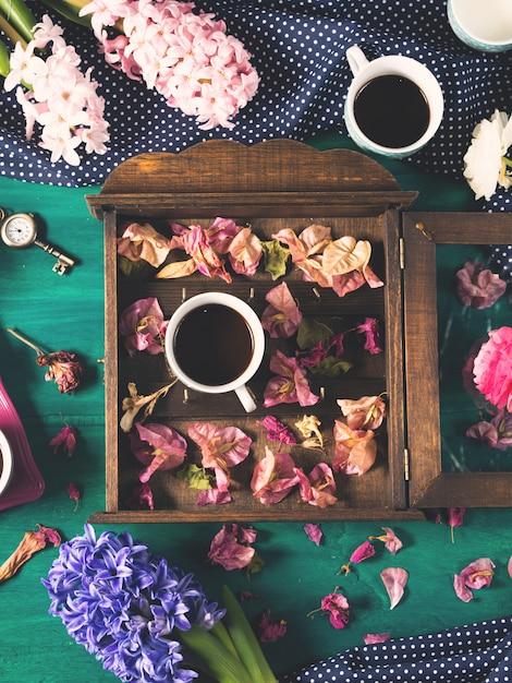 Café et fleurs sur fond sombre Photo Premium