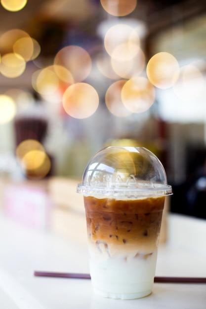 Café froid dans une tasse en plastique sur une table en bois dans un café Photo Premium