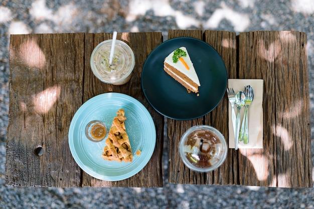 Café et gâteau l'après-midi sur une table en bois dans le jardin Photo Premium
