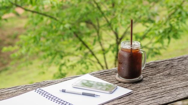 Café glacé americano, smartphone, stylo et livre sur une table en bois. Photo Premium