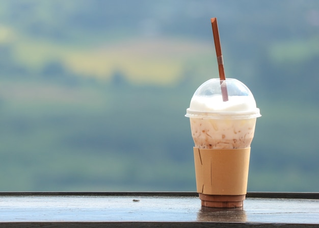 Un café glacé dans une tasse en plastique avec vue naturelle en arrière-plan. Photo Premium
